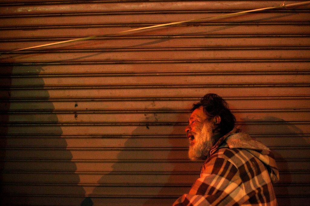 . Jesse Raca, a 58-year-old homeless alcoholic, leans on the shutters of a closed store while trying to sleep in the Skid Row area of Los Angeles, Tuesday, March 19, 2013. (AP Photo/Jae C. Hong)