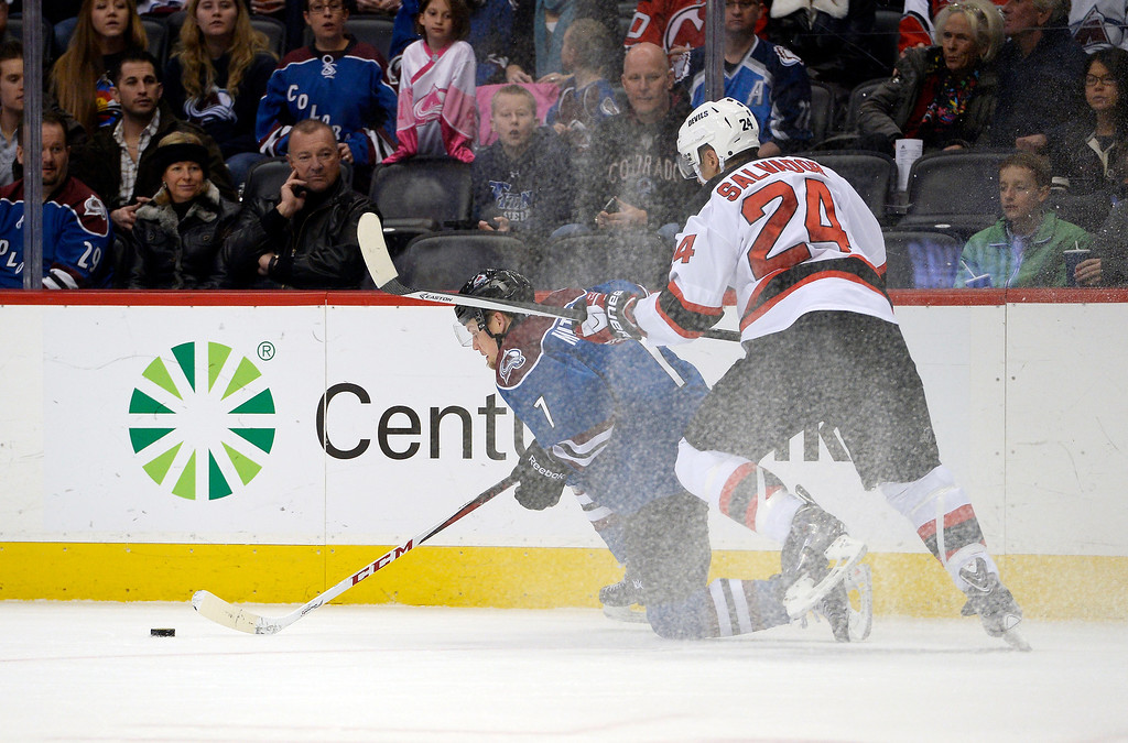 . Colorado Avalanche center John Mitchell (7) falls to the losing control of the puck as New Jersey Devils defenseman Bryce Salvador (24) defends on the play during the first period  January 16, 2014 at Pepsi Center. (Photo by John Leyba/The Denver Post)