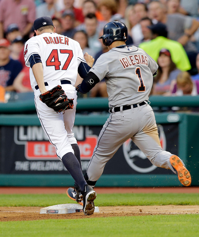 . Detroit Tigers\' Jose Iglesias (1) reaches an infield single ahead of the tag by Cleveland Indians starting pitcher Trevor Bauer (47) in the fourth inning of a baseball game Monday, June 22, 2015, in Cleveland. (AP Photo/Tony Dejak)