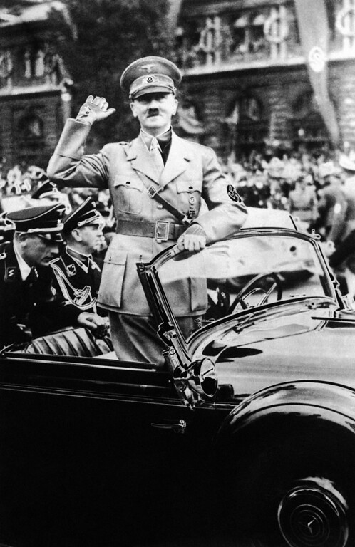 . 1938: Adolf Hitler. German Chancellor Adolf Hitler standing in his car greeting crowds on the way from the station in Nuremberg, Germany, to the Deutscher Hof Hotel after his arrival, on Sept. 5, 1938. (AP Photo)