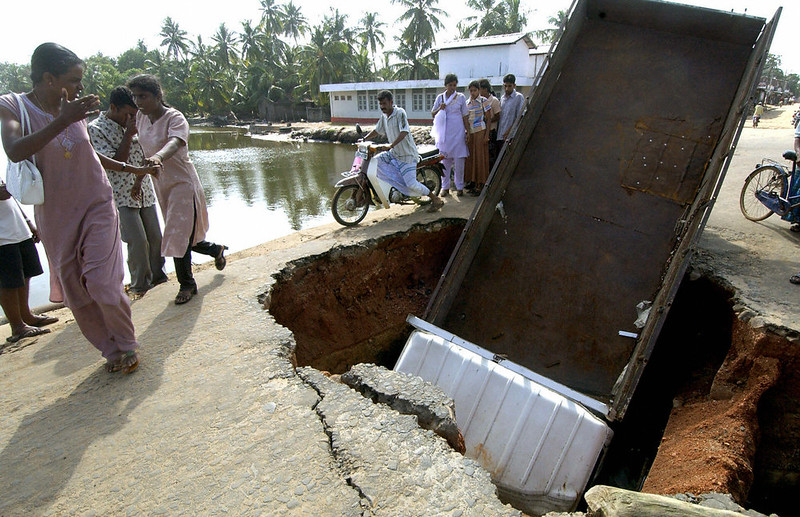 . Sri Lankan residents walk past an overturned truck lying inside a crater formed on the main bridge on the island of Kinniya some 250 kms north-east of the Sri lankan capital Colombo 28 December 2004.  Kinniya island is one of the worst affected areas of the island nation after giant tsunami waves devastated two thirds of the country\'s shoreline in Sri Lanka\'s worst ever disaster. Mass funerals of thousands of tsunami victims got underway Tuesday in Sri Lanka as volunteers pulled more decomposed corpses from washed out trains, cars and smashed buildings. The confirmed death toll rose to 12,909 as burials were carried out along southern coastal areas, with the first in the town of Matara, 160 kilometres (100 miles) south of here.   INDRANIL MUKHERJEE/AFP/Getty Images