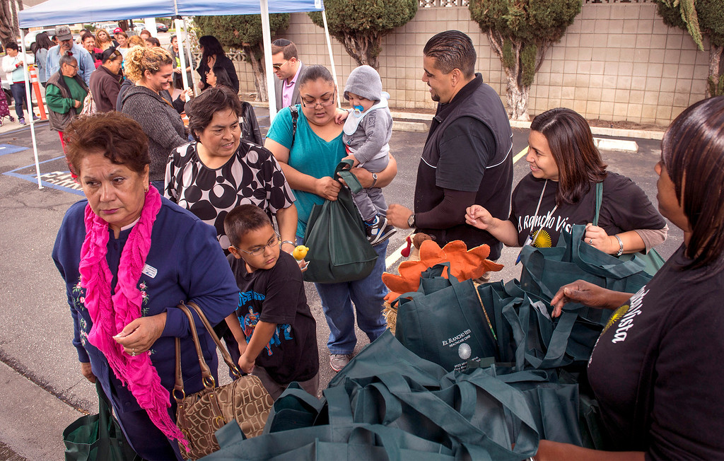 . El Rancho Vista Healthcare Center workers Noe Ramirez and Veronica Guzman, center right, pass out Thanks giving turkeys to some of the 200 families at the Pico Rivera, Calif. facility on Mines Avenue Nov. 21, 2013.  (Staff photo by Leo Jarzomb/Whittier Daily News)