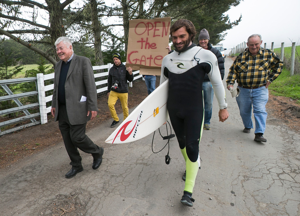 . Former California Congressman Pete McCloskey, left, and surfer Joao Demacedo lead a group of activists down the entrance to  Martin\'s Beach in Half Moon Bay, Calif., on Thursday, March 14, 2013. Martin\'s Beach was closed to public access in 2008 when the property was purchased by venture capitalist Vinod Khosla. McCloskey joined members of the Surfrider Foundation and other public activists for a protest outside the gate to Martin\'s beach for public access to the beach to be restored. On Tuesday, the Surfrider Foundation filed suit a law suit citing the beach closure is in violation of the California Coastal Act. (John Green/Staff)