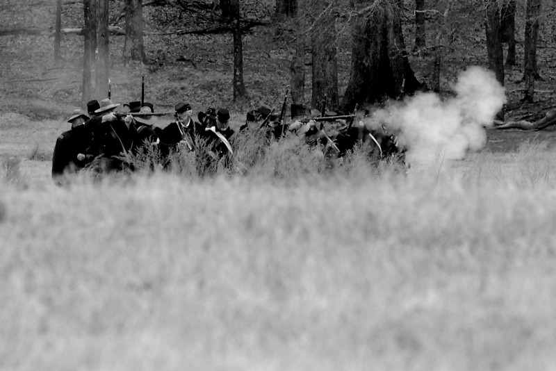 Union reenactors fire while moving across the battlefield. The Skirmish at Gamble's Hotel happened on March 5, 1885 when 500 federal soldiers, under the command of Reuben Williams of the 12th Indiana Infantry, marched into Florence to destroy the railroad depot but were met by Confederate soldiers backed up with 400 militia. The reenactment, held by the 23rd South Carolina Infantry, was held at the Rankin Plantation in Florence, South Carolina on Saturday, March 5, 2011. Photo Copyright 2011 Jason Barnette