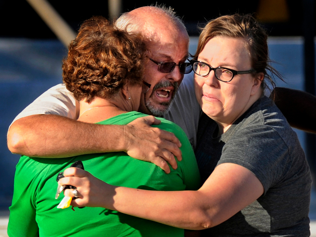 . Tom Sullivan, center, hugs his wife Terry, left, and daughter Megan outside Gateway High School, Friday July 20, 2012, in Aurora. Sullivan came to the place where police brought witnesses and victims to search for his son Alex who had gone to see the movie. Alex, one of the twelve people killed in the theater, died on his 27th birthday. RJ Sangosti, The Denver Post