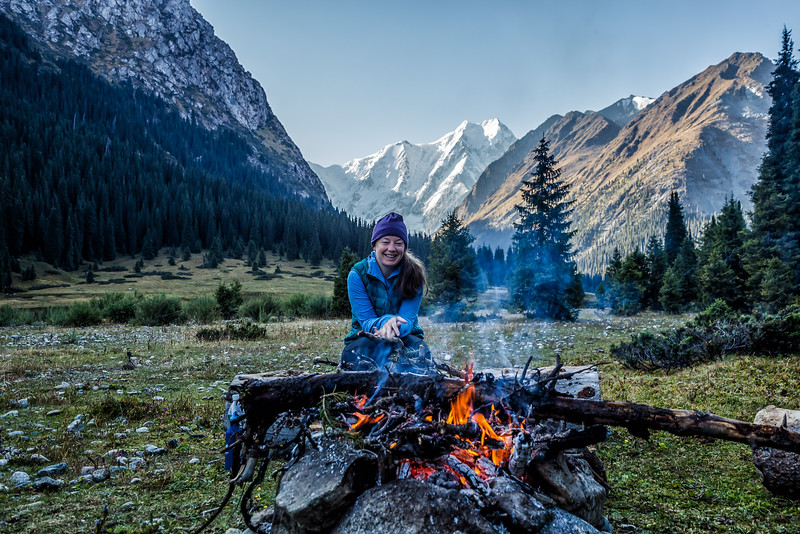 Lina Stock sitting at a campfire in the mountains of Kyrgyzstan