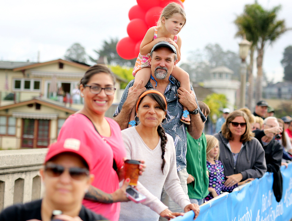 . Onlookers watch as runners make their way past the finish line in Capitola on Sunday during the 42nd annual Wharf to Wharf. (Kevin Johnson -- Santa Cruz Sentinel)