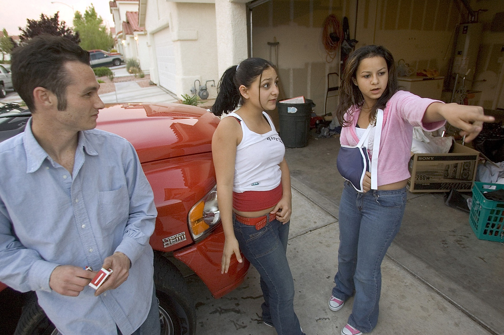 . Genesis Reyes, 13, right, describes how police detained her and allegedly hurt her arm as they executed a search warrant at the Las Vegas home of her mother, Anna Ayala, Thursday, April 7, 2005. Looking on are family friend Ken Bono, 24, who lives at the residence, and cousin Priscilla Chavarin, 16. Ayala, who claims she bit into a human finger while eating chili at a Wendy\'s restaurant, has a history of filing lawsuits, including a claim against another fast-food restaurant. (AP Photo/Las Vegas Review-Journal, K.M. Cannon)