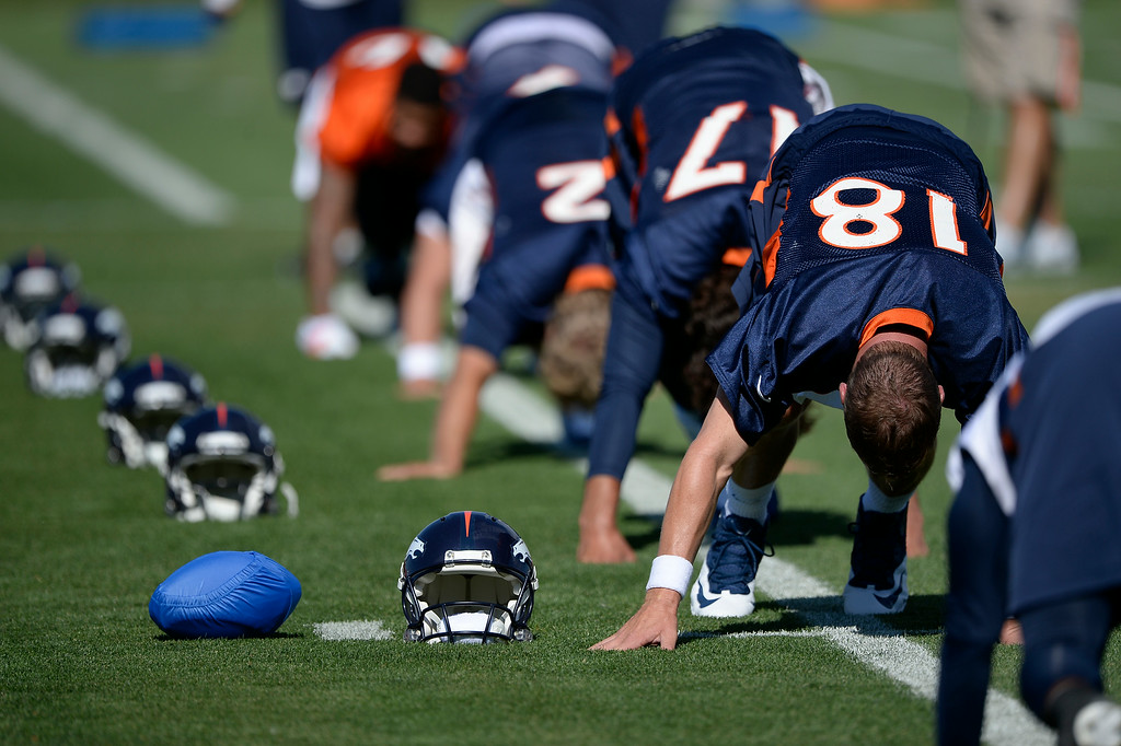 . Denver Broncos quarterback Peyton Manning (18) sets his football in a blue cover next to his helmet during the start of the Denver Broncos 2014 training camp July 24, 2014 at Dove Valley. (Photo by John Leyba/The Denver Post)