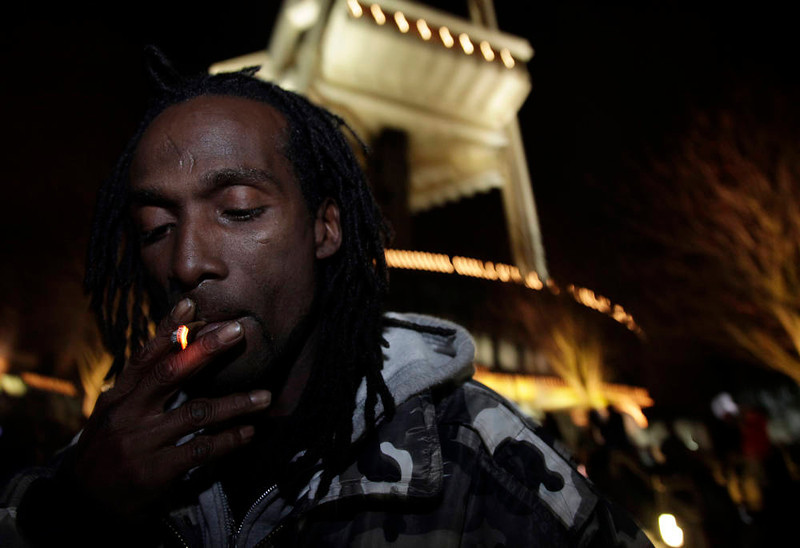 . Allister Adams smokes marijuana, Thursday, Dec. 6, 2012, just after midnight at the Space Needle in Seattle. Possession of marijuana became legal in Washington state at midnight, and several hundred people gathered at the Space Needle to smoke and celebrate the occasion, even though the new law does prohibit public use of marijuana. (AP Photo/Ted S. Warren)