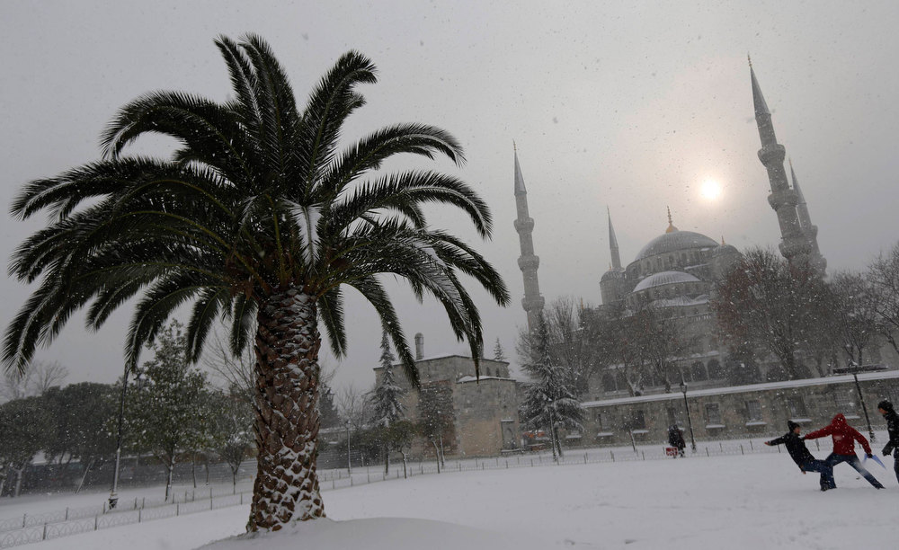 . Boys play in the courtyard of the Sultanahmet mosque, known as the Blue mosque, during a snow storm in Istanbul January 8, 2013. REUTERS/Murad Sezer