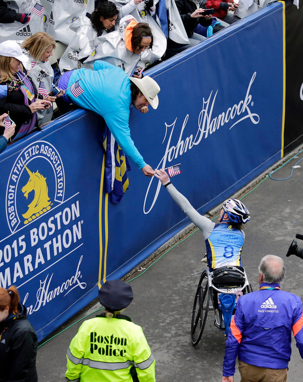 . Carlos Arredondo, left, a 2013 Boston Marathon first-responder, hands Tatyana McFadden, of Russia, a U.S. flag after she won the women\'s wheelchair division of the Boston Marathon, Monday, April 20, 2015, in Boston. (AP Photo/Charles Krupa)