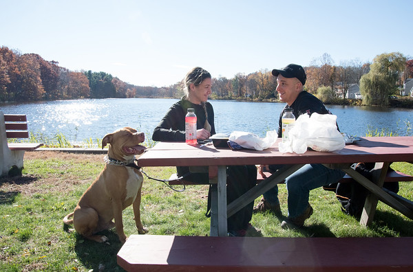 11/07/18 Wesley Bunnell | Staff Sarah Smith and Frank Tirabassi enjoy their lunch outdoors next to Paper Goods Pond on a warm Wednesday afternoon as Sarah's dog Mason looks on.