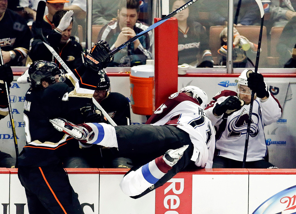 . Anaheim Ducks right wing Bobby Ryan, left, knocks Colorado Avalanche right wing Milan Hejduk into the bench during the third period of an NHL hockey game in Anaheim, Calif., Sunday, Feb. 24, 2013. The Ducks won 4-3 in overtime. (AP Photo/Chris Carlson)
