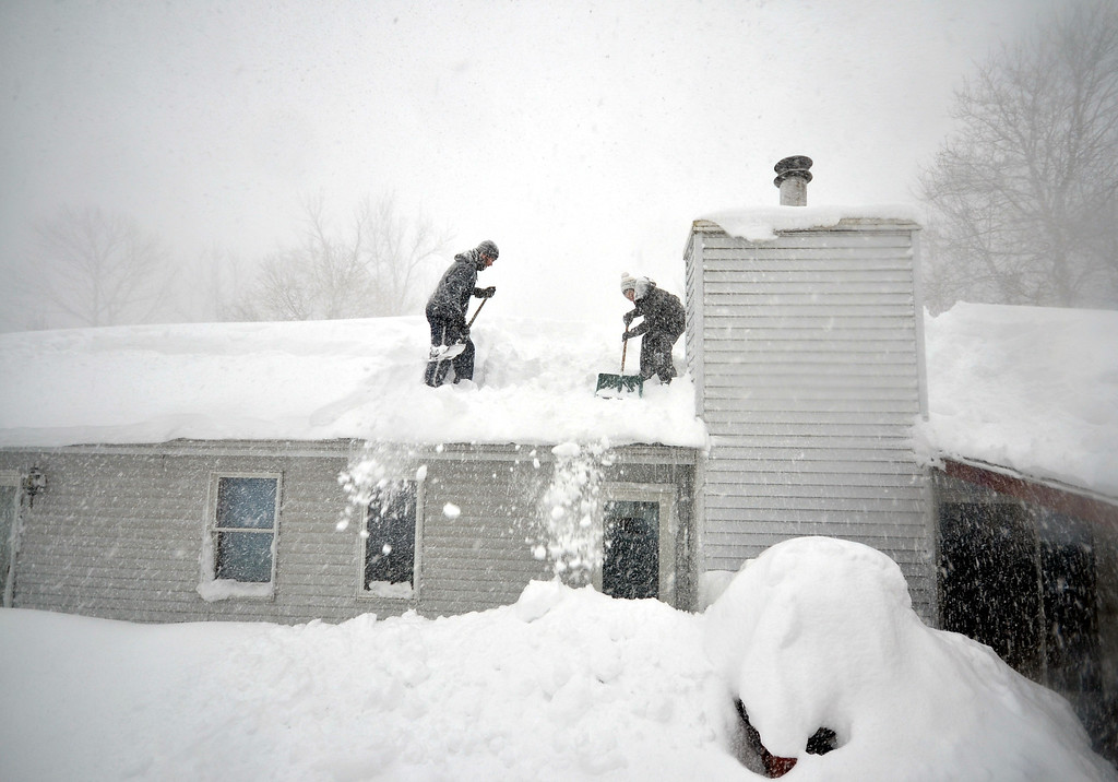 . BUFFALO, NY - NOVEMBER 20, 2014: Tami Normile and Richard Brooks attempt to remove some of the five feet of snow from a roof top on November 20, 2014 in the Lakeview neighborhood of Buffalo, New York. The record setting Lake effect snowstorm dumped up to six feet of snow in less than 24 hours closing a one hundred mile section of The New York State Thruway as well as other major roads around Buffalo. Seven deaths have already been  attributed to the storm and a second round beginning late Wednesday evening will bring up to three more feet of snow overnight and into Thursday.  (Photo by John Normile/Getty Images)