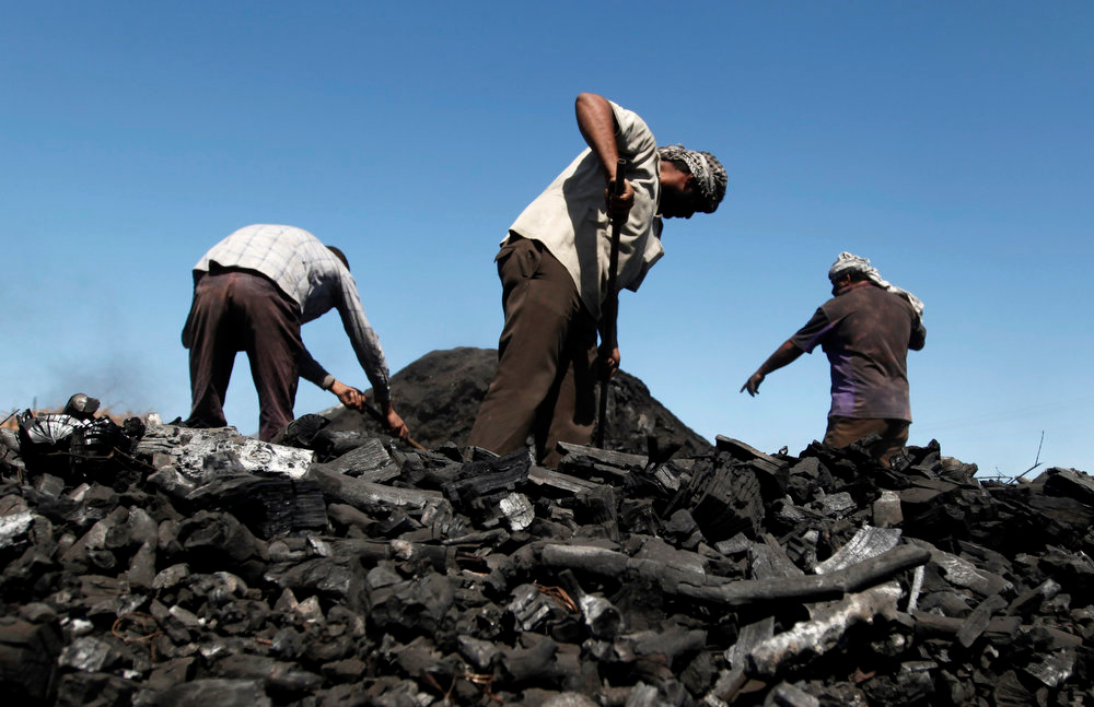 . Palestinian workers remove coal from a pile at one of the few local charcoal manufacturing shops east of Gaza City on March. 24, 2013. In adapting to years of border blockades and shortages, Gazans have become experts at recycling and making new out of old, including turning scrap wood into charcoal to be used for barbecue grills and water pipes in local restaurants and coffee houses. (AP Photo/Hatem Moussa)