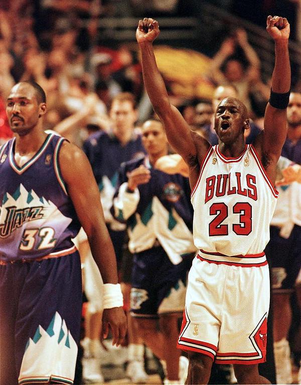 . CHICAGO, IL - JUNE 14:  Michael Jordan (R) of the Chicago Bulls jumps in the air as Karl Malone (L) of the Utah Jazz walks off the court 13 June after game six of the 1997 NBA Finals at the United Center in Chicago, Illinois. Jordan was named the series MVP, leading the Bulls to a 4-2 series win over the Utah Jazz.  (PETER PAWINSKI/AFP/Getty Images)