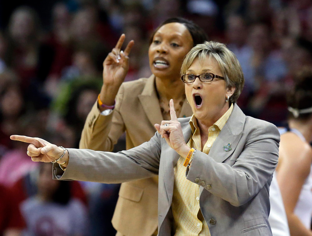 Description of . Tennessee head coach Holly Warlick, right, and assistant coach Kyra Elzy, left, shout to their team in the first half of a regional semifinal game against Oklahoma in the women's NCAA college basketball tournament in Oklahoma City, Sunday, March 31, 2013. (AP Photo/Sue Ogrocki)