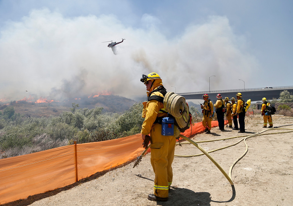 . Firefighters watch from a ridge as a helicopter drops retardant on a out-of- control wild fire Tuesday, May 13, 2014, in San Diego.  (AP Photo)