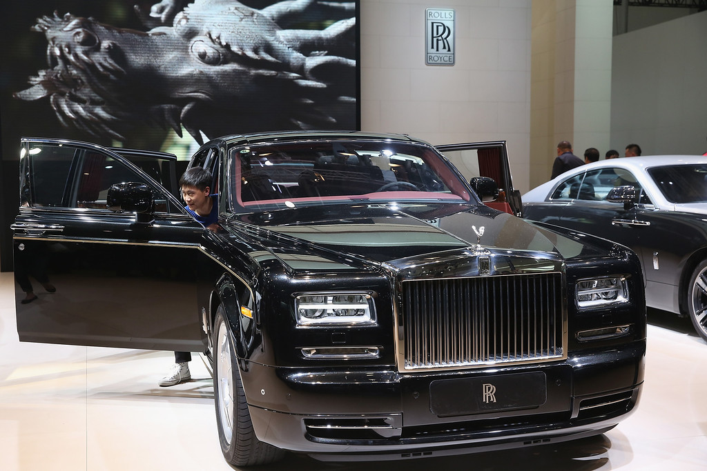 . The potential consumer looks at a Rolls-Royce Phantom car during the 2014 Beijing International Automotive Exhibition at China International Exhibition Center on April 21, 2014 in Beijing, China. (Photo by Feng Li/Getty Images)
