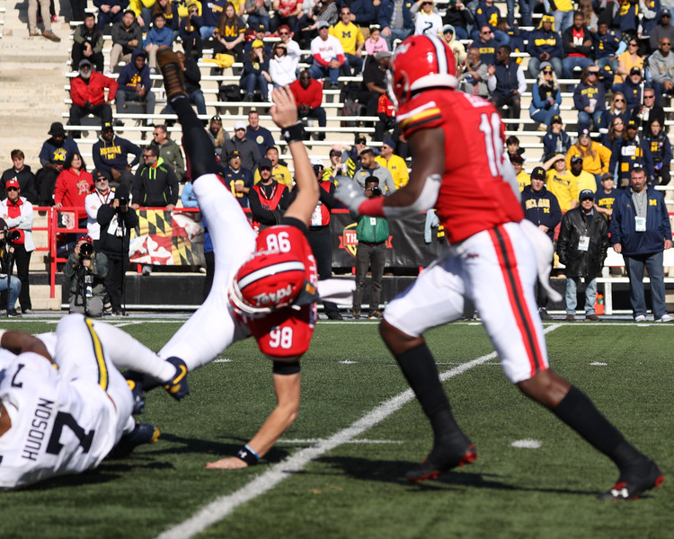 Michigan LB Khaleke Hudson rolls into Maryland P Anthony Pecorella.