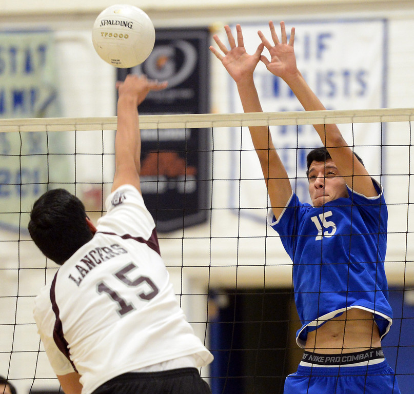 . El Rancho\'s Bryan Rojas (#15) jumps up to block a shot from Bell Gardens\' Bryan Diaz (#15) in their non-league game at El Rancho High School in Pico Rivera on Friday March 28, 2014. Bell Gardens defeated El Rancho 3-2 games. (Staff Photo by Keith Durflinger/Whittier Daily News)