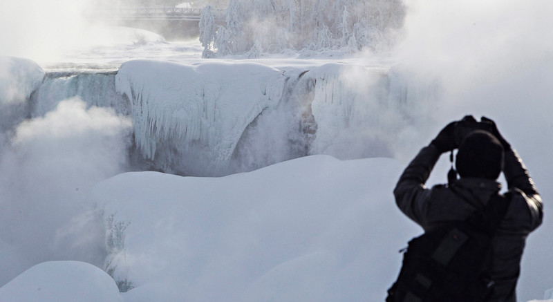 . A man photographs ice masses formed around the American Falls as seen from Niagara Falls, Ontario, Canada, Thursday, Feb. 19, 2015. (AP Photo/The Canadian Press,Aaron Lynett)