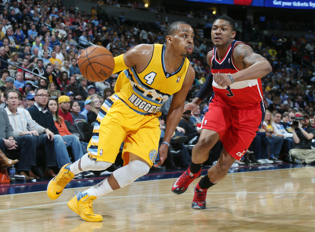 . Denver Nuggets guard Randy Foye (4) works ball inside for shot past Washington Wizards\' Bradley Beal in the third quarter of the Nuggets\' 105-102 victory in an NBA basketball game in Denver on Sunday, March 23, 2014. (AP Photo/David Zalubowski)