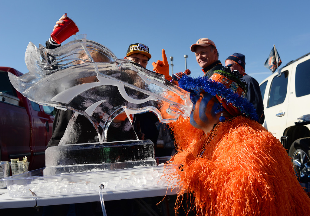 . Denver Broncos fan Paul Marinaccio takes a shoot from ice sculpture as he and other fans tailgate outside at Sports Authority Field at Mile High, January, 17, 2016. The Denver Broncos will take on Pittsburgh Steelers during AFC division playoff game. (Photo by RJ Sangosti/The Denver Post)