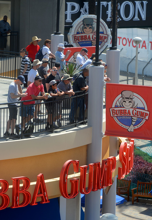 . Race fans watch the action from atop Bubba Gumps restaurant with views of turns two and three in Long Beach, CA on Friday, April 17, 2015. The 40th annual Toyota Grand Prix of Long Beach kicked off with practices for all of the racing divisions. (Photo by Scott Varley, Daily Breeze)