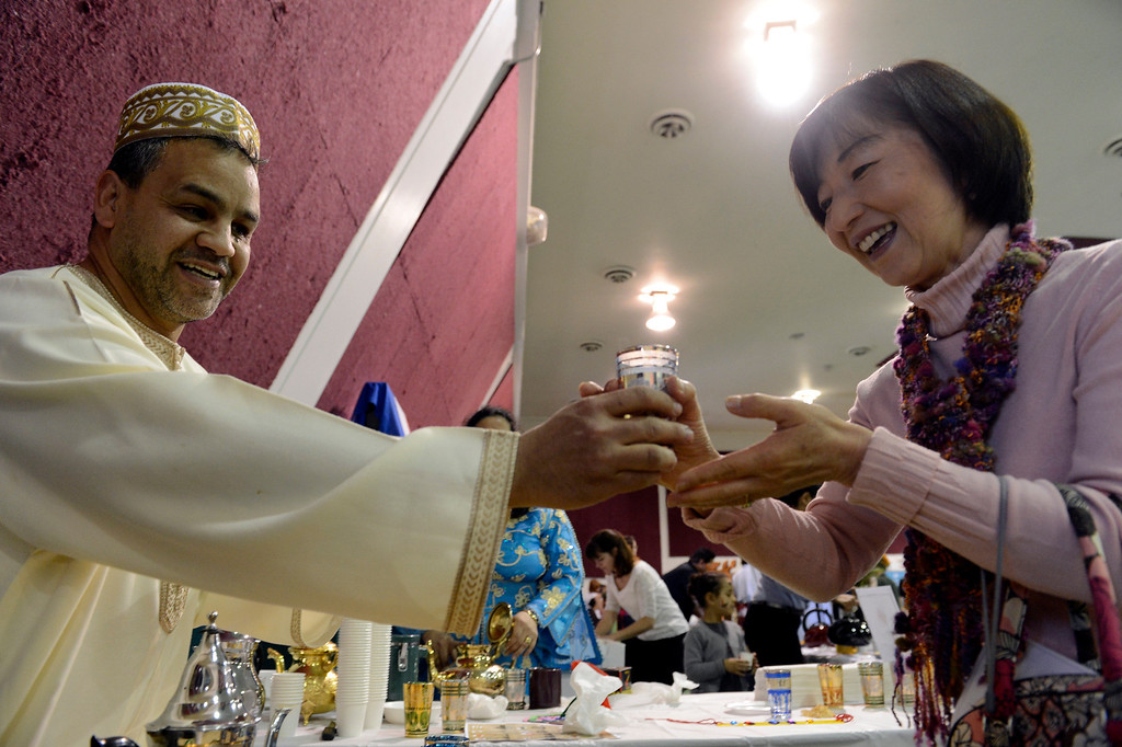 . DENVER, CO. - JANUARY 27: Kebir Assougdam from Morocco hands a cup of tea to Keiko Goldman 50-years-old during the World Tea Fair at Denver Montclair International School January 27, 2013. There were 12 tables featuring tea samples from around the World.  (Photo By John Leyba / The Denver Post)