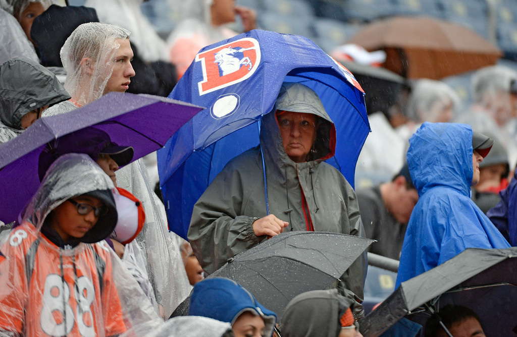 . Denver Broncos fans brave the rain as they attend day six of the Denver Broncos 2014 training camp July 30, 2014 at Sports Authority Field at Mile High Stadium.  (Photo by John Leyba/The Denver Post)