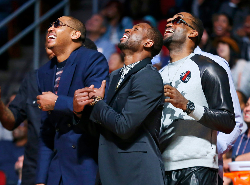 . NBA players Carmelo Anthony, Dwyane Wade and LeBron James (L-R) watch the slam dunk contest during the NBA basketball All-Star weekend in Houston, Texas, February 16, 2013. REUTERS/Jeff Haynes
