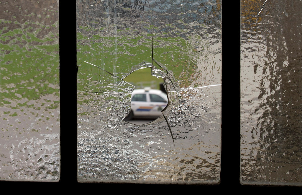 . An RCMP police car is seen through broken glass in the rotunda of the Parliament buildings, Thursday Oct. 23, 2014 in Ottawa.   (AP Photo/The Canadian Press, Adrian Wyld)