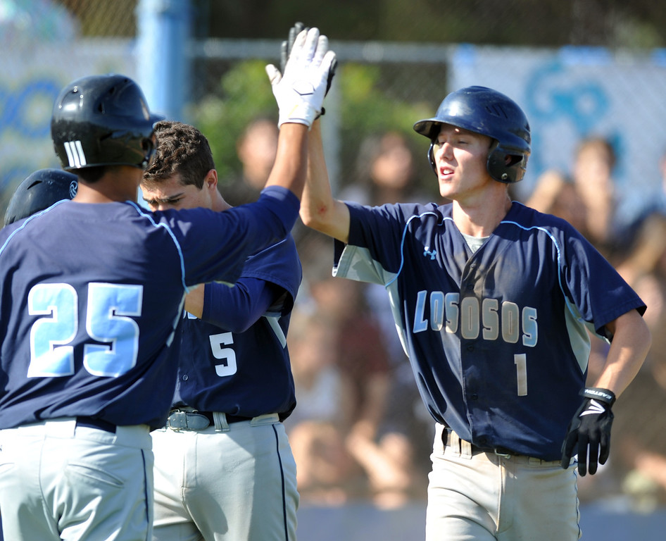 . Los Osos\' Chris Butcher (#1) is congratulated after scoring in their CIF quarterfinal baseball game at La Mirada High School on Friday May 24, 2013. Los Osos beat La Mirada 8-5. (SGVN/Staff Photo by Keith Durflinger)