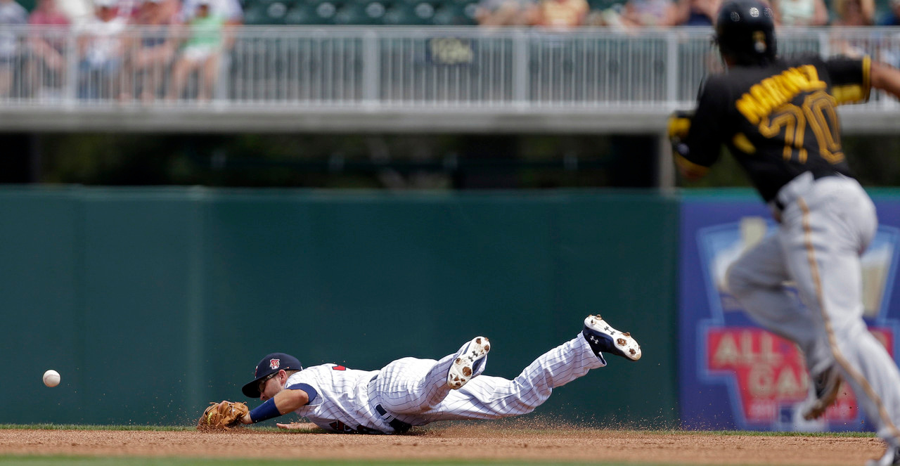 . Twins second baseman Brian Dozier dives for a grounder single as Pirates shortstop Michael Martinez advances to second in the first inning. (AP Photo/Gerald Herbert)