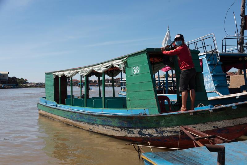 Man standing on tourboat in Tonle Sap lake, Kampong Phluk, Siem Reap, Cambodia