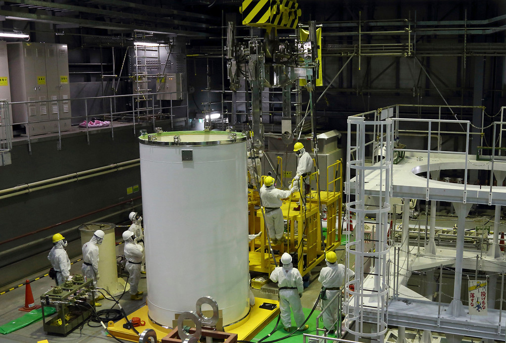 . Workers wearing protective suits and masks work on a crane for a transport container in preparation for the removal of spent nuclear fuel inside the building housing the Unit 4 reactor at the Fukushima Dai-ichi nuclear power plant in Okuma, Fukushima, northeastern Japan, Thursday, Nov. 7, 2013.  (AP Photo/Tomohiro Ohsumi, Pool)