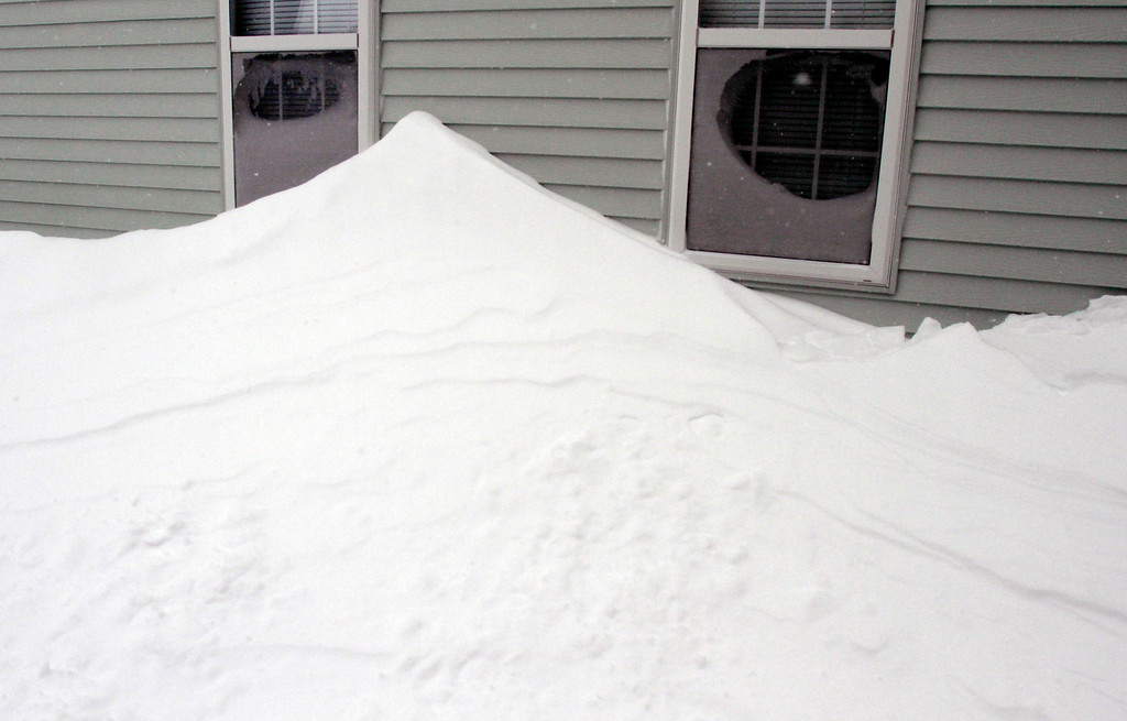 . Drifted snow is piled along the wall of a house after a winter storm, Tuesday, Jan. 27, 2015, in Marlborough, Mass. A storm packing blizzard conditions spun up the East Coast early Tuesday, pounding parts of coastal New Jersey northward through Maine with high winds and heavy snow. (AP Photo/Bill Sikes)