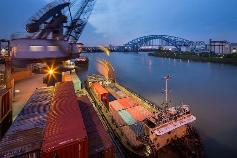 A crane loads a container barge on the Dongping waterway in Nanhai District, Foshan, Guangdong Province, China. Liwan District, Guangzhou, can be seen on the far opposite shore in the center of the frame.