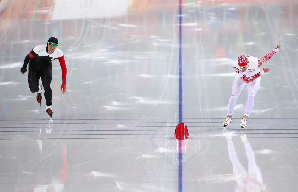 . Vincent De Haitre of Canada and Denis Yuskov of Russia compete during the Men\'s 1000m Speed Skating event during day 5 of the Sochi 2014 Winter Olympics at at Adler Arena Skating Center on February 12, 2014 in Sochi, Russia.  (Photo by Streeter Lecka/Getty Images)