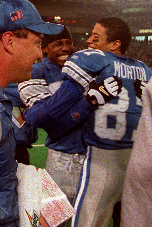 . Detroit Lions Head Coach Marty Mornhinweg (left) watches as Desmond Howard (center) hugs wide receiver Johnnie Morton (right) after the team\'s first win of the season-- a 27-24 defeat of the Minnesota Vikings at the Silverdome Sunday.  The Lions are now 1-12.