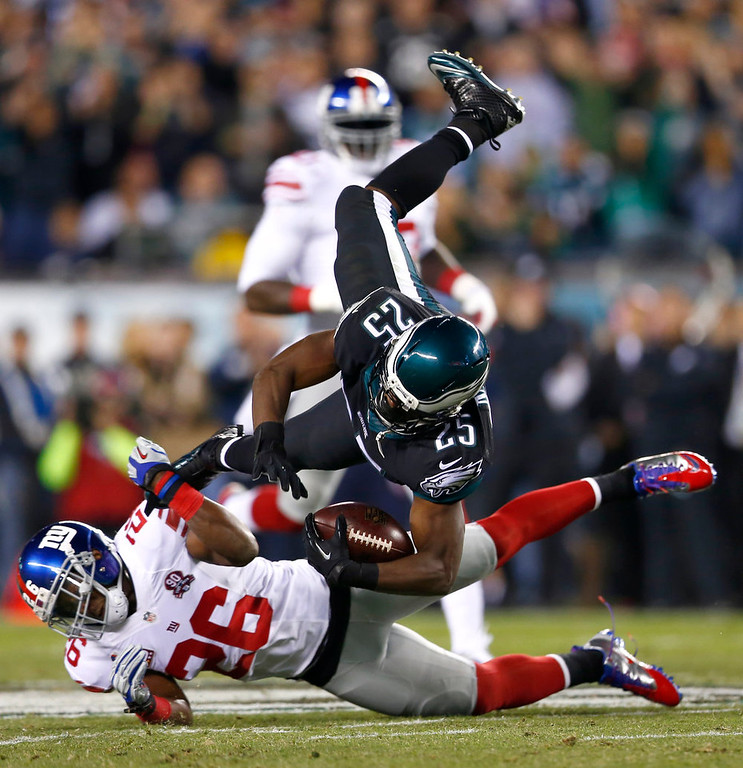 . Philadelphia Eagles running back LeSean McCoy (25) is hit by New York Giants strong safety Antrel Rolle (26) during the first half of an NFL football game, Sunday, Oct. 12, 2014, in Philadelphia. (AP Photo/Matt Rourke)
