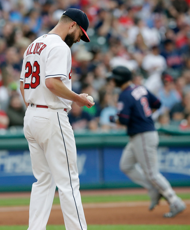 . Cleveland Indians starting pitcher Corey Kluber, left, waits for Minnesota Twins\' Brian Dozier to run the bases after Dozier hit a two-run home run during the fourth inning of a baseball game Friday, June 15, 2018, in Cleveland. (AP Photo/Tony Dejak)