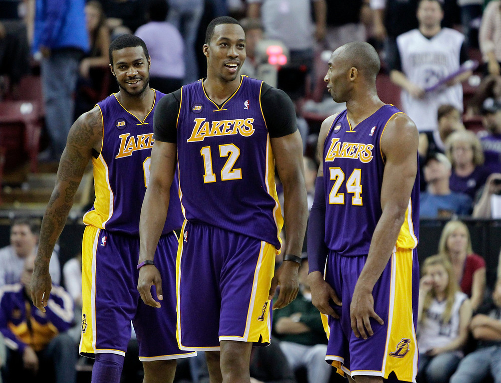 . Los Angeles Lakers\' Earl Clark, left, Dwight Howard, center, and Kobe Bryant smile during the closing moments of the Lakers 103-98 win over the Sacramento Kings in an NBA basketball game in Sacramento, Calif., Saturday, March 30, 2013. (AP Photo/Rich Pedroncelli)
