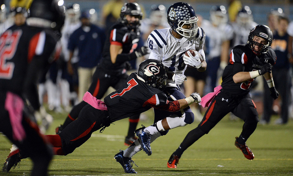 . Los Osos\' Donovan Williams (16) runs for a first down as Glendora\'s Collin Grady (7) makes the tackle in the first half of a prep football game at Citrus College in Glendora, Calif., on Thursday, Oct. 31, 2013.    (Keith Birmingham Pasadena Star-News)
