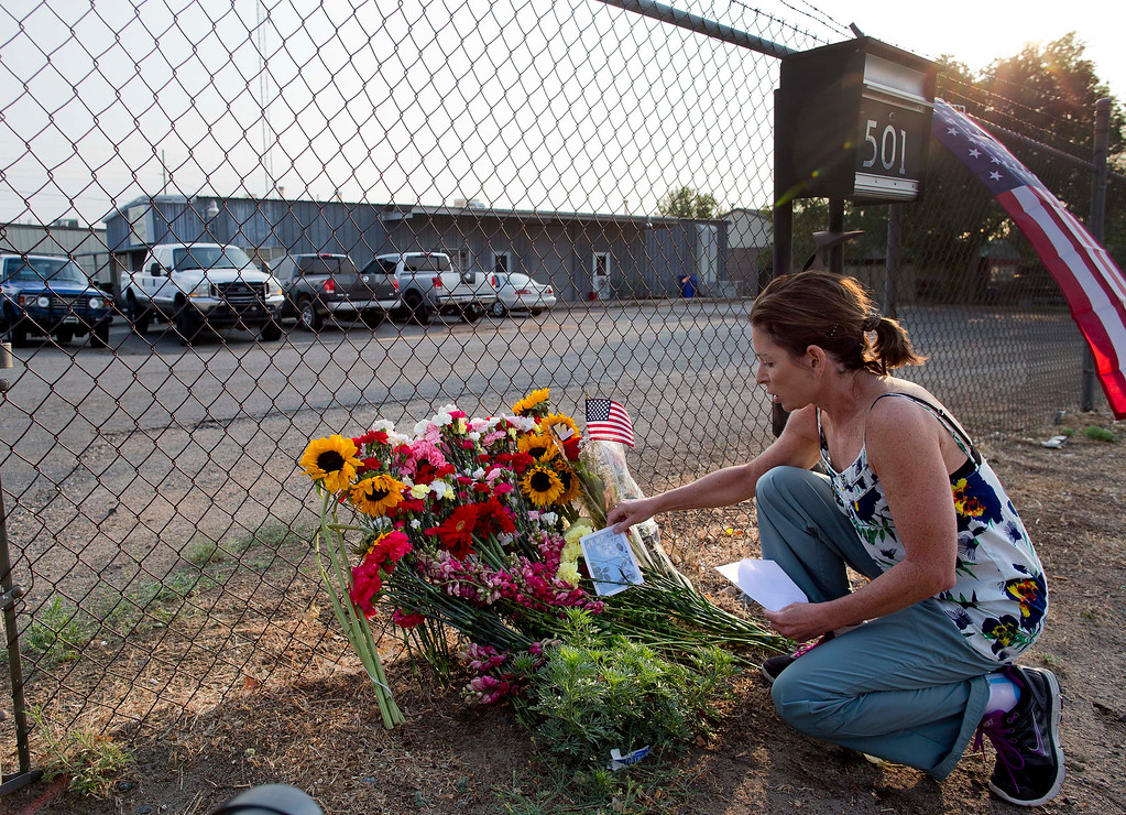 . Toby Schultz lays flowers at the gate of the Granite Mountain Hot Shot Crew fire station, Monday, July 1, 2013, in Prescott, Ariz. (AP Photo/Julie Jacobson)