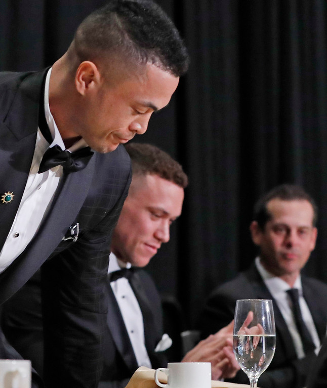 . National League Most Valuable Player Giancarlo Stanton, left, takes his seat after accepting his award, as American League Rookie of the Year Aaron Judge, center, applauds with New York Yankees manager Aaron Boone, right looking on during the New York Chapter of the Baseball Writers\' Association of America annual dinner in New York, Sunday, Jan. 28, 2018. (AP Photo/Kathy Willens)