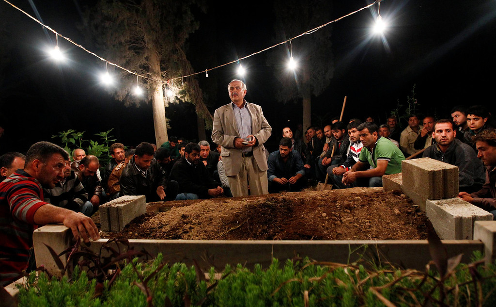 . A man reads from the Koran as others listen during the funeral of 55-year-old Kemal Baz, a victim of a car bomb attack, in the town of Reyhanli in Hatay province near the Turkish-Syrian border May 15, 2013. Baz was one of the 50 people to have been killed by two bomb attacks in Reyhanli over the weekend. Turkey\'s prime minister will push U.S. President Barack Obama for more assertive action on Syria during a visit to Washington this week, days after car bombs tore through Reyhanli in the deadliest spillover of violence yet. REUTERS/Umit Bektas