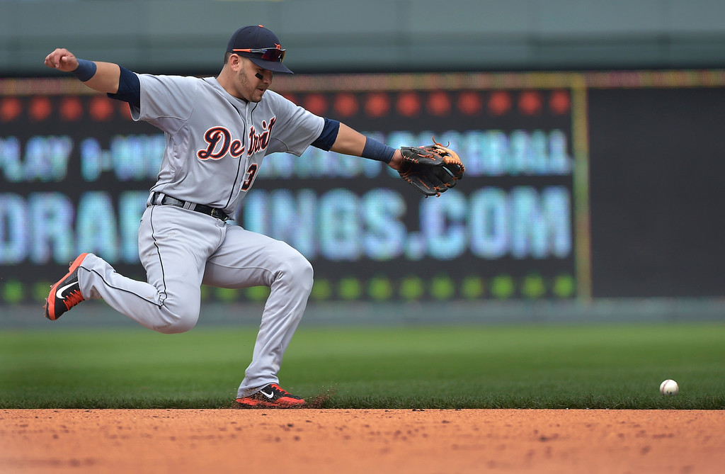 . Detroit Tigers shortstop Eugenio Suarez (30) is unable get to a grounder hit by Kansas City Royals shortstop Alcides Escobar (2) for an RBI single during the fifth inning of a baseball game Saturday, Sept. 20, 2014, in Kansas City, Mo. (AP Photo/Reed Hoffmann)